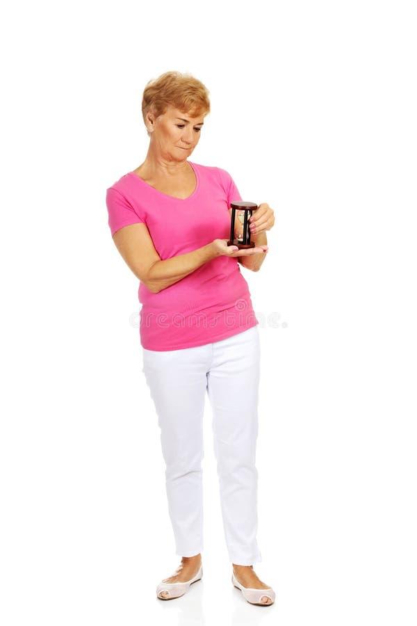 Femme supérieure de sourire tenant des sandglass photo stock