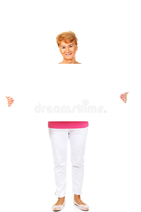 Femme supérieure de sourire tenant la bannière vide photographie stock libre de droits