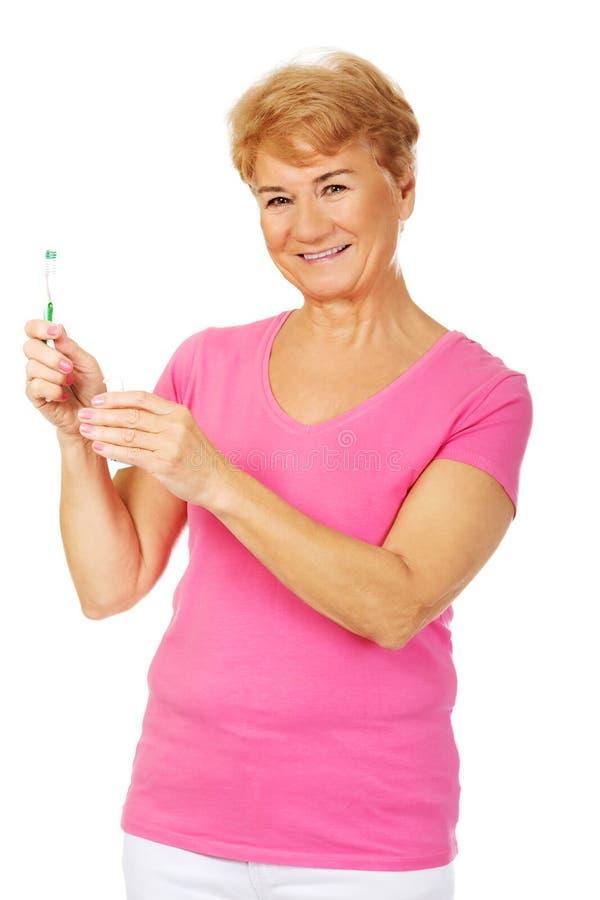 Femme supérieure de sourire tenant la pâte dentifrice et la brosse à dents photographie stock