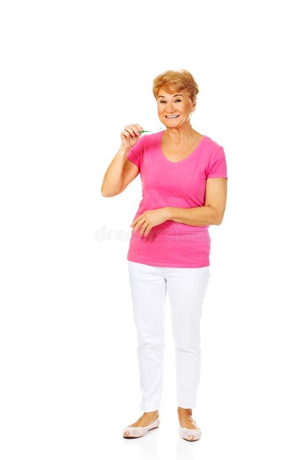 Femme supérieure de sourire tenant la pâte dentifrice et la brosse à dents photos stock