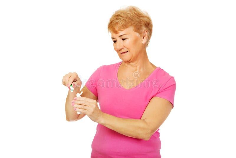 Femme supérieure de sourire tenant la pâte dentifrice et la brosse à dents photos libres de droits