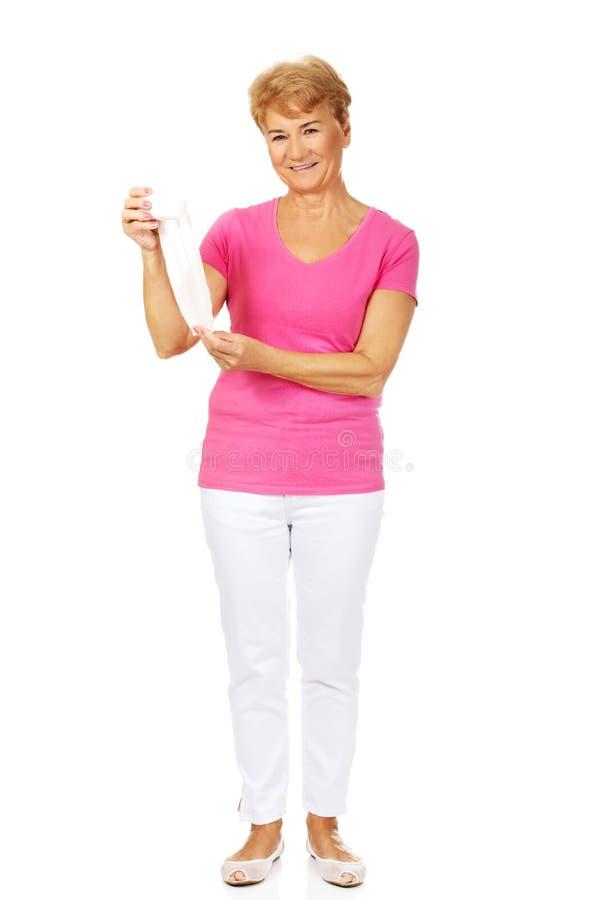 Femme supérieure de sourire tenant le bandage images stock