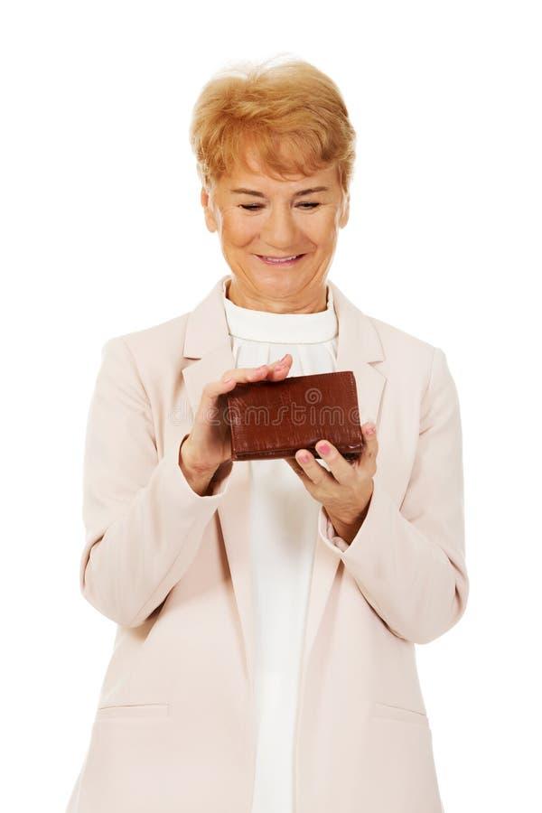 Femme supérieure de sourire tenant le portefeuille image libre de droits