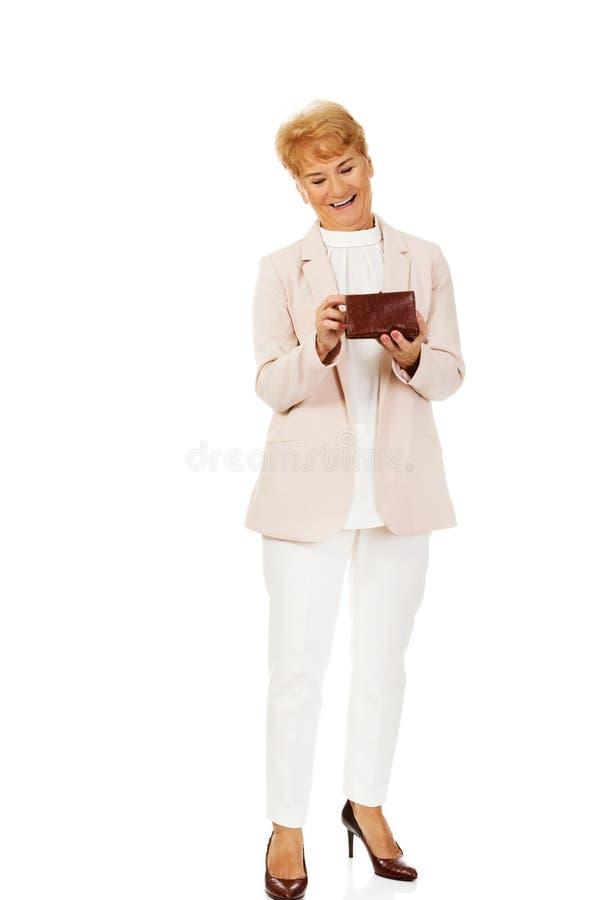 Femme supérieure de sourire tenant le portefeuille photo stock