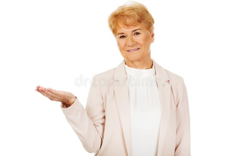 Femme supérieure de sourire tenant quelque chose sur la paume ouverte image libre de droits