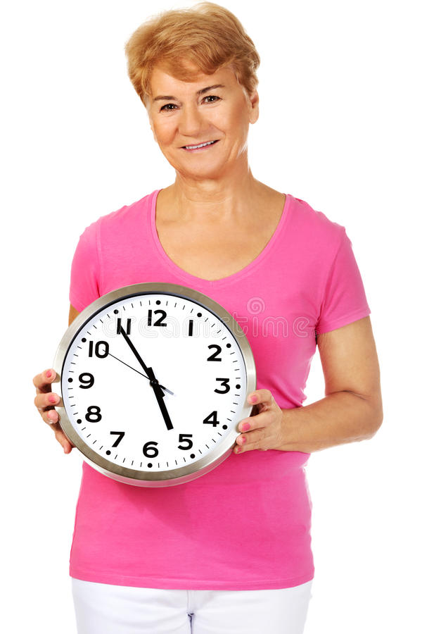 Femme supérieure de sourire tenant une horloge photos stock