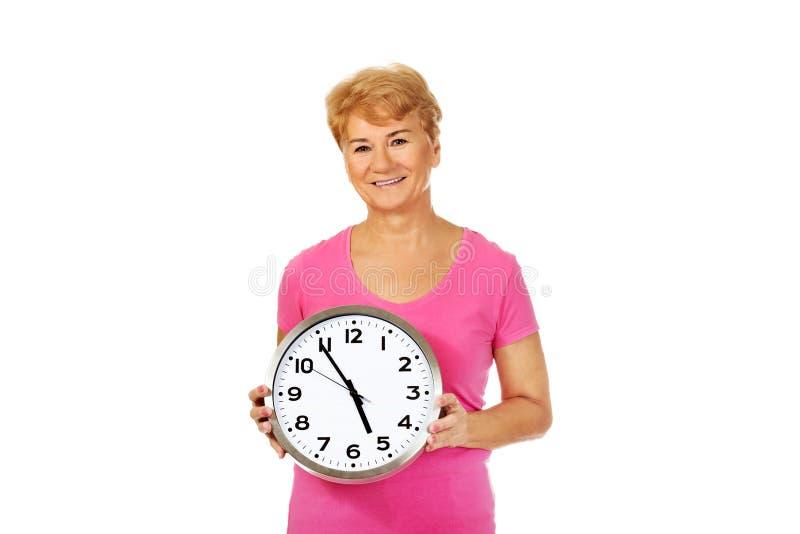 Femme supérieure de sourire tenant une horloge photo libre de droits