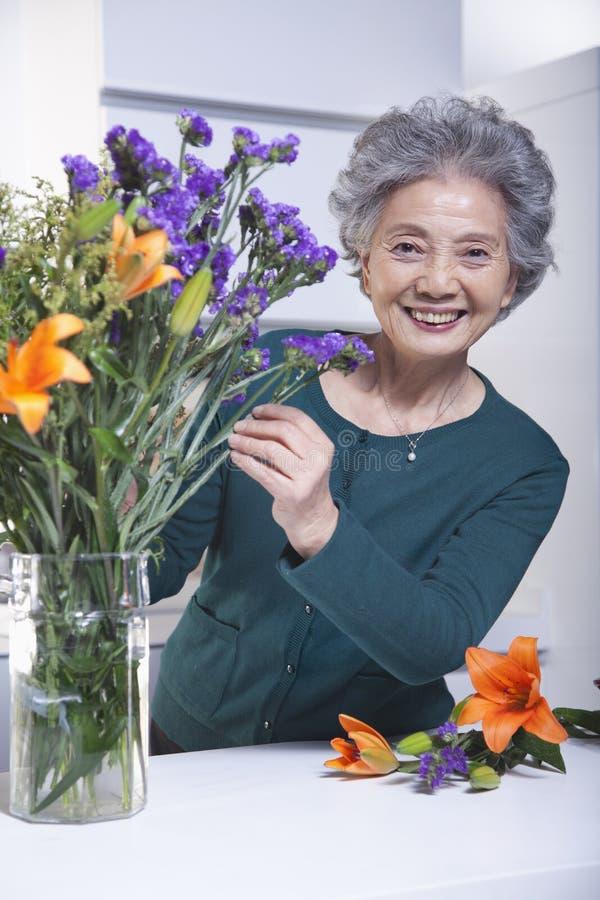 Femme supérieure de sourire touchant un bouquet des fleurs dans la cuisine, portrait images stock