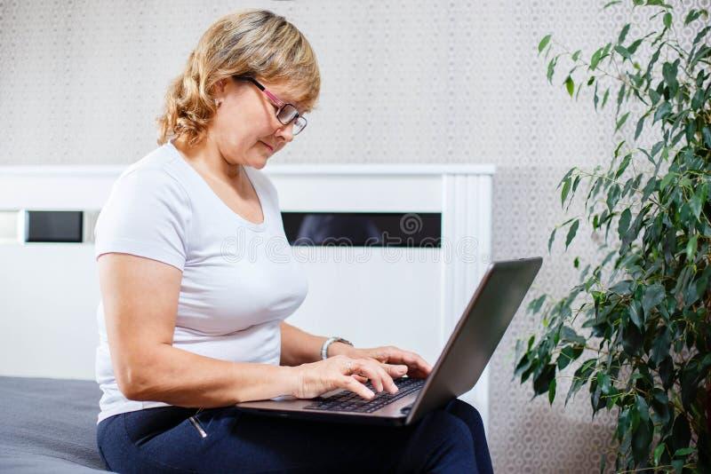 Femme supérieure de sourire travaillant sur l'ordinateur portable à la maison photographie stock libre de droits