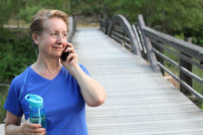 Femme supérieure de touristes employant la communication futée de voyage de parc d'arbre de vert de vacances d'été de sourire d'a photo libre de droits