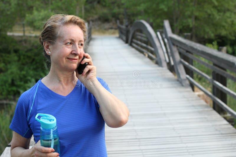 Femme supérieure de touristes employant la communication futée de voyage de parc d'arbre de vert de vacances d'été de sourire d'a images libres de droits