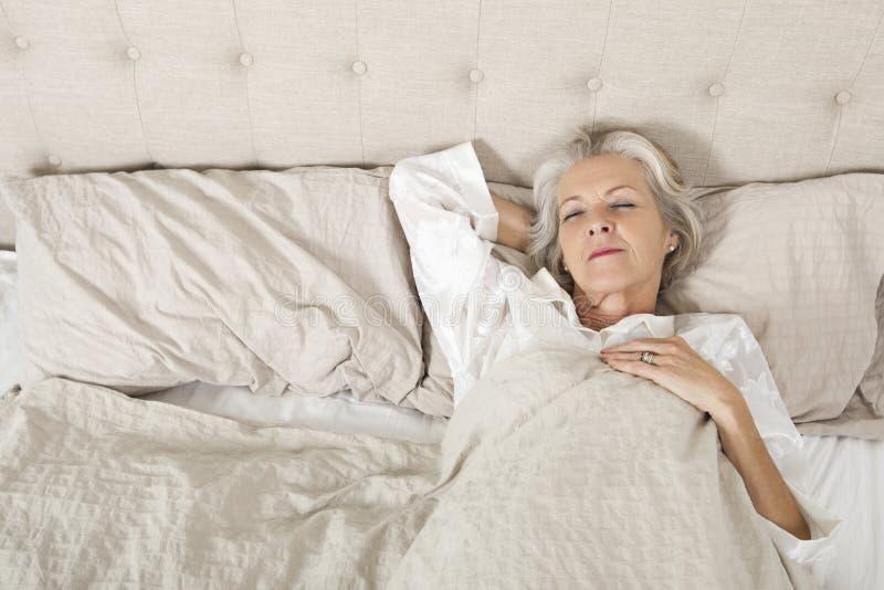 Femme supérieure dormant dans le lit photographie stock