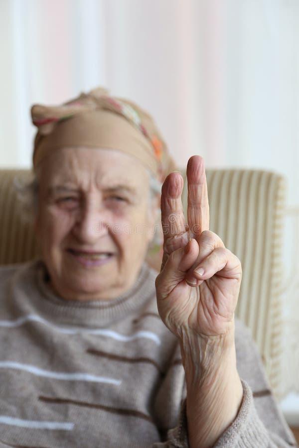 Femme supérieure effectuant le signe de victoire photo libre de droits