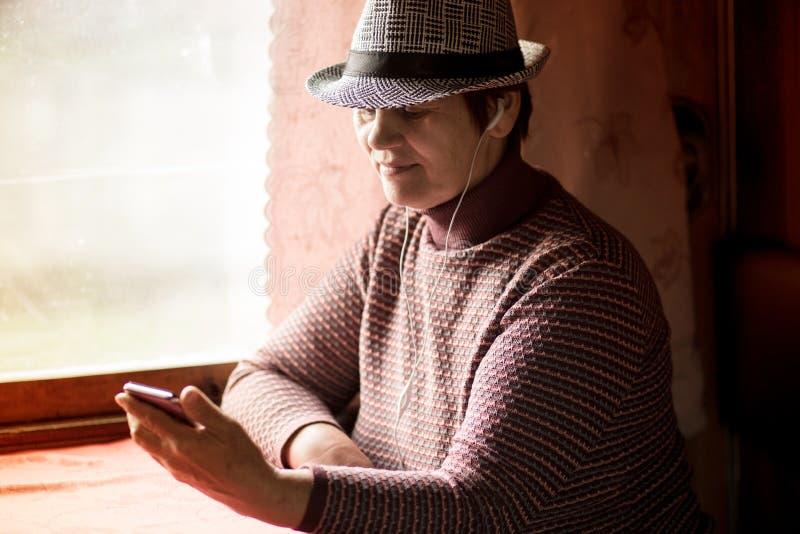 Femme supérieure employant l'application mobile sur le smartphone au billet de train et d'achat en ligne images stock