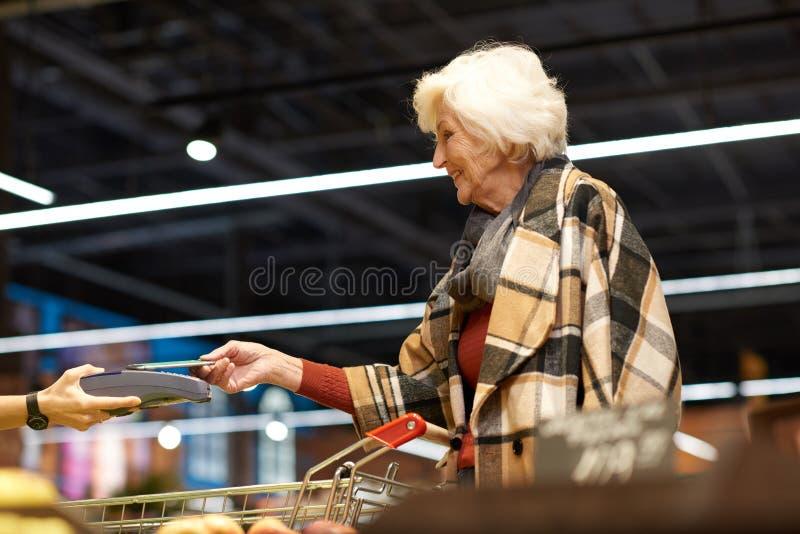 Femme supérieure employant le NFS dans le supermarché images stock