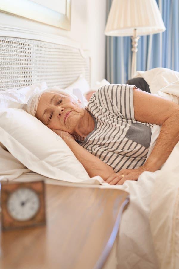 Femme supérieure endormie dans son lit pendant le matin images libres de droits