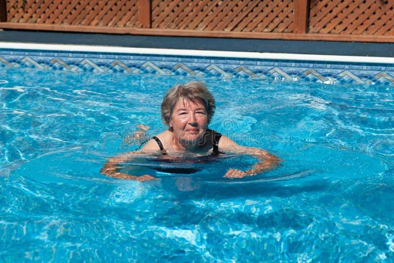 Femme supérieure essayant de nager photographie stock