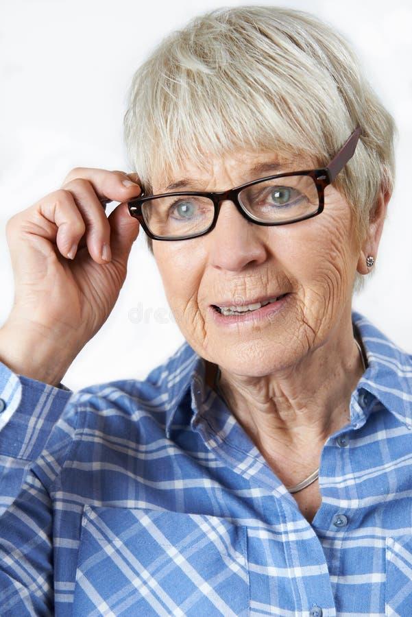Femme supérieure essayant sur de nouveaux verres photos libres de droits