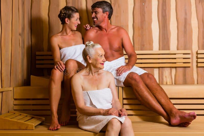 Femme supérieure et couples suant dans le sauna image stock