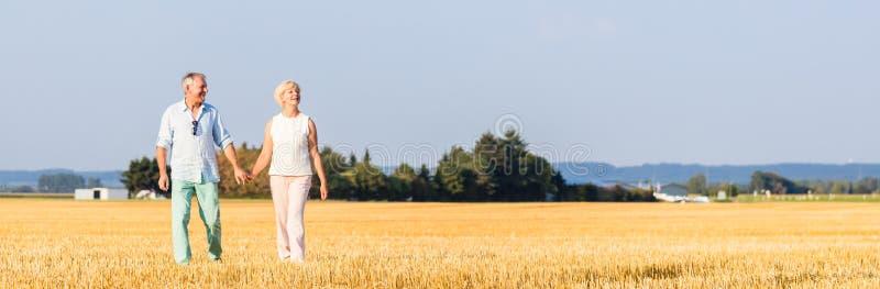 Femme supérieure et homme tenant des mains ayant la promenade images stock