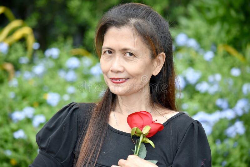 Femme supérieure féminine diverse retirée heureuse avec une fleur images stock