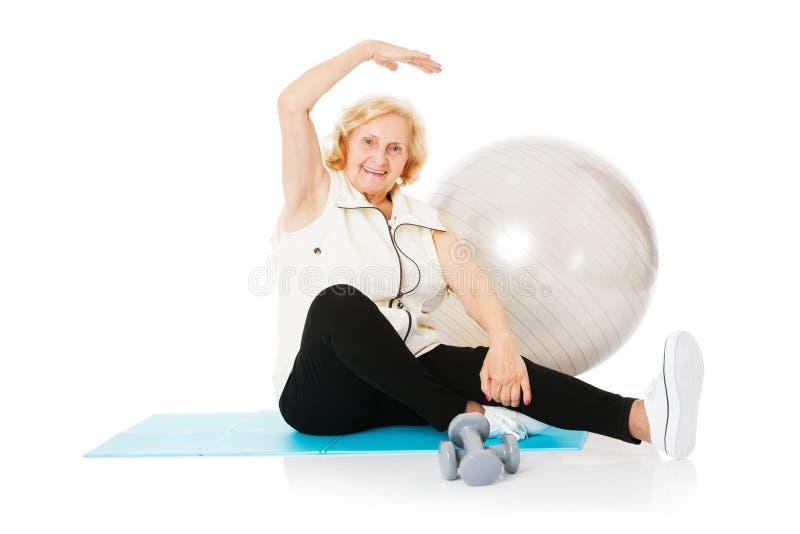 Femme supérieure faisant étirant l'exercice sur le tapis images stock