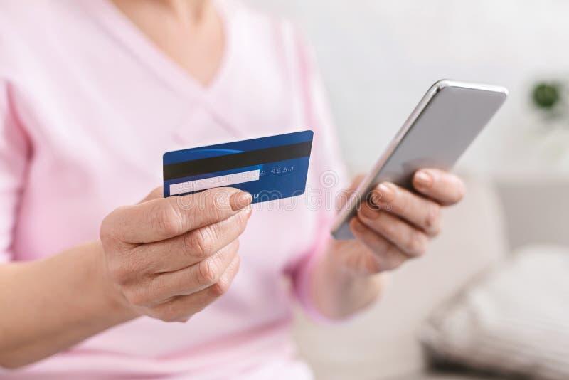 Femme supérieure faisant des emplettes en ligne avec la carte de crédit et le téléphone photographie stock libre de droits
