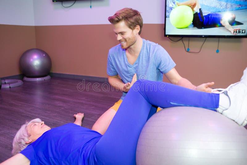 Femme supérieure faisant des pilates avec le physiothérapeute image libre de droits