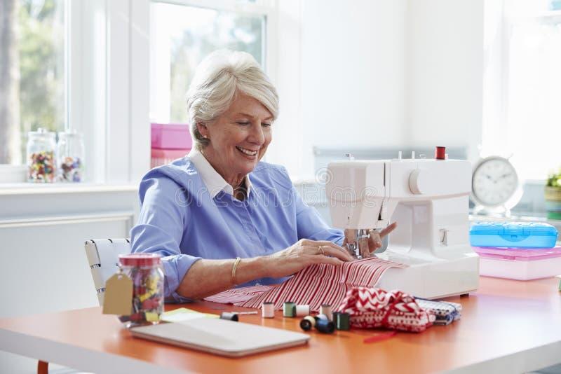 Femme supérieure faisant des vêtements utilisant la machine à coudre à la maison images libres de droits