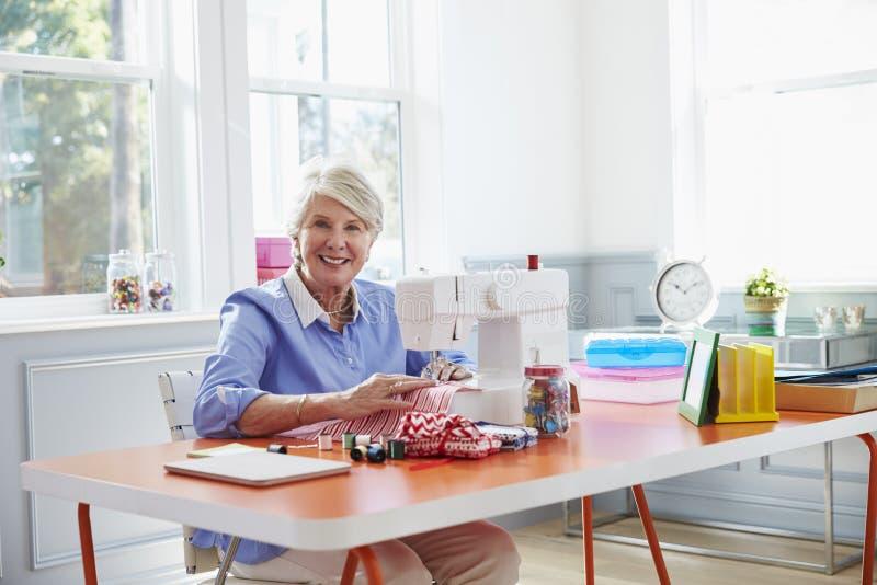 Femme supérieure faisant des vêtements utilisant la machine à coudre à la maison photos stock