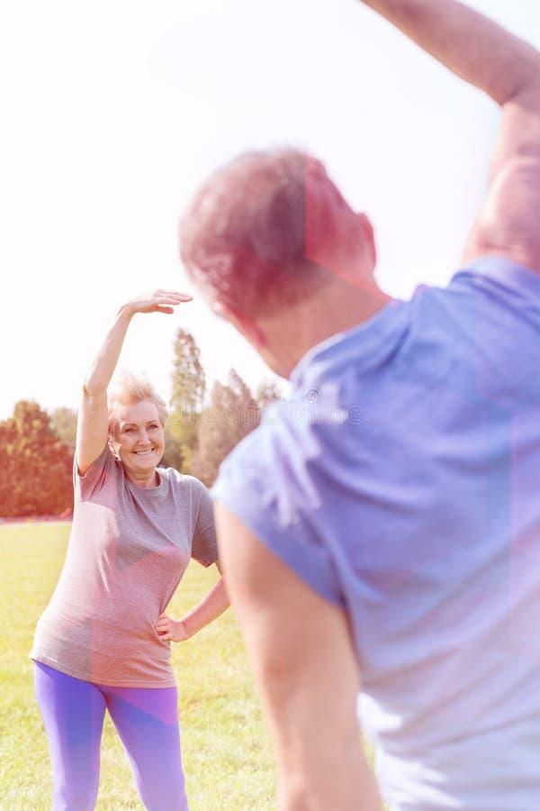 Femme supérieure faisant l'exercice latéral de courbure avec l'homme en parc photo libre de droits