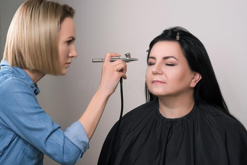 Femme supérieure faisant le maquillage dans le salon de beauté Maquillage avec l'aérographe Le professionnel compensent les femme photographie stock