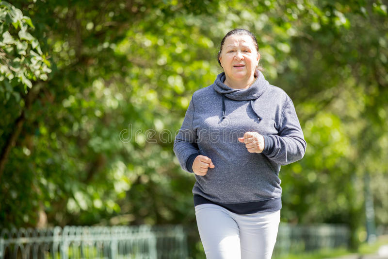 Femme supérieure faisant le sport en parc photographie stock