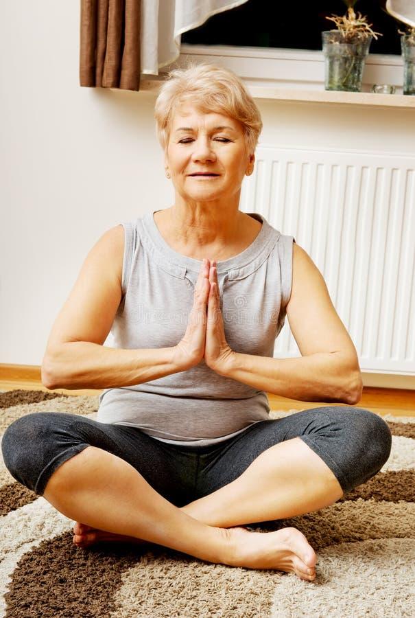 Femme supérieure faisant le yoga dans le salon photographie stock
