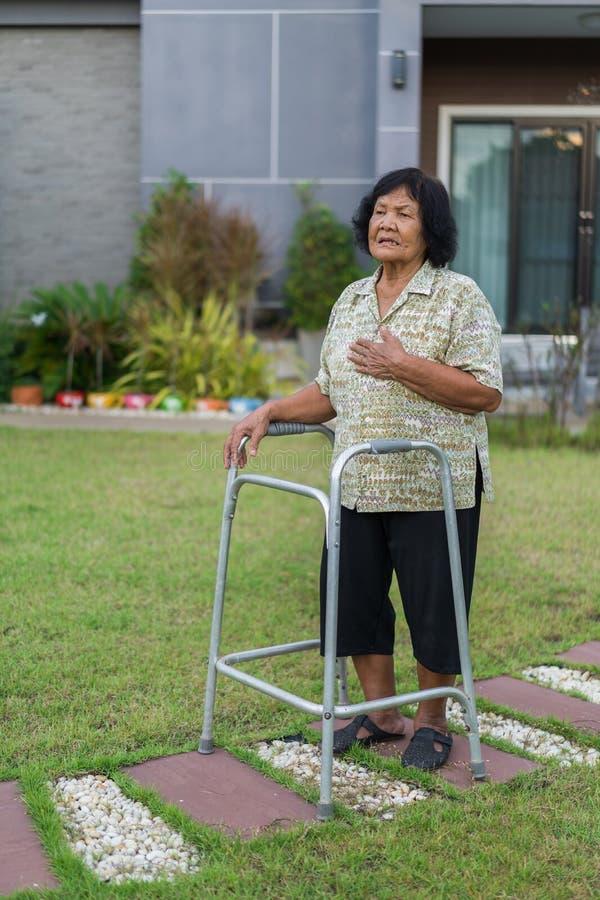 Femme supérieure fatiguée ayant le problème de coeur après marche avec le walke photo libre de droits
