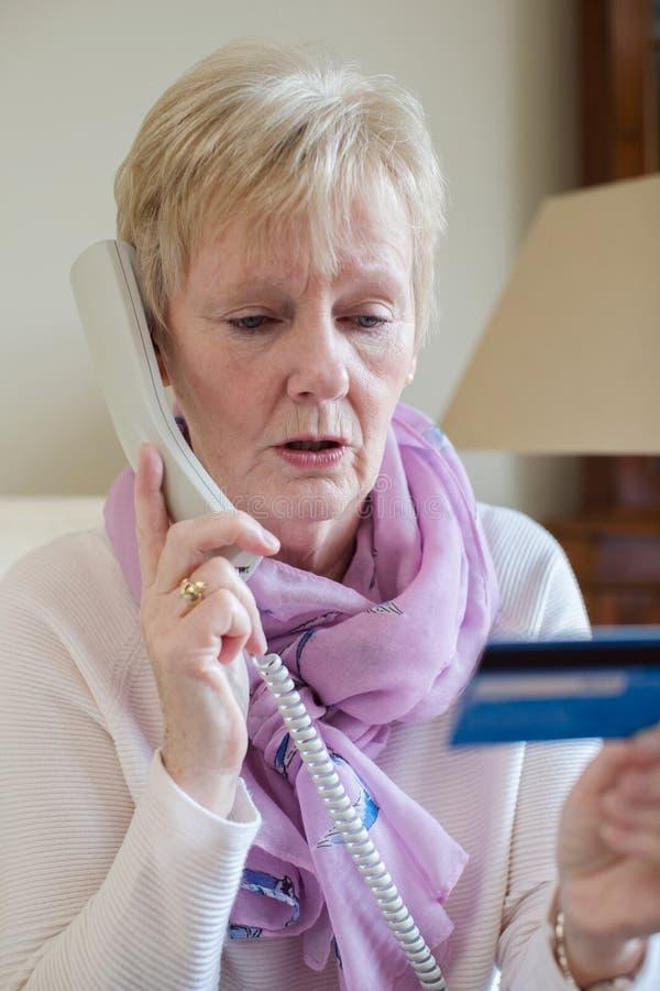 Femme supérieure fournissant des détails de carte de crédit au téléphone photo stock