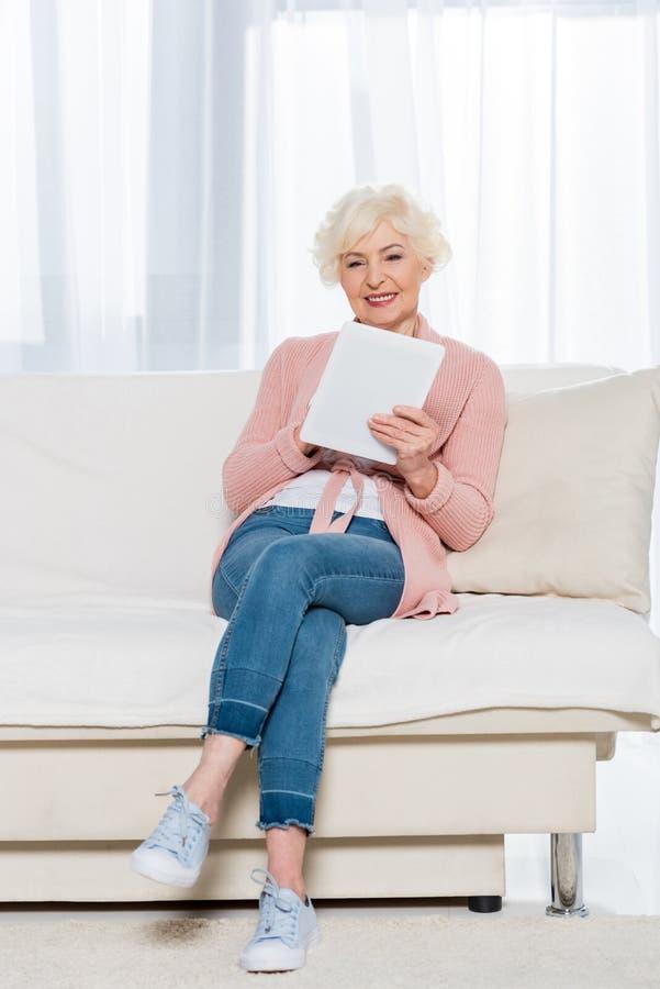 femme supérieure gaie s'asseyant sur le sofa et à l'aide du comprimé numérique photo libre de droits