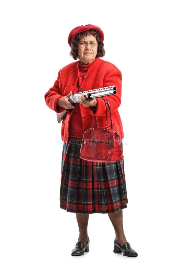 Femme supérieure grincheuse avec un fusil de chasse photos stock