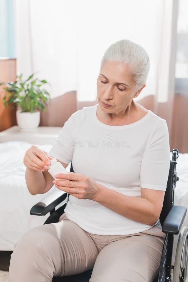 femme supérieure handicapée dans le fauteuil roulant tenant le récipient image stock