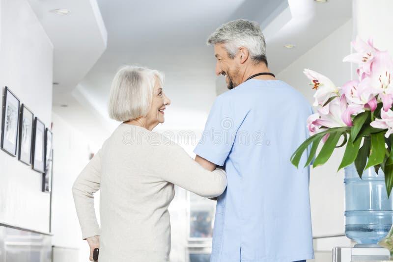 Femme supérieure handicapée regardant le physiothérapeute mûr images libres de droits
