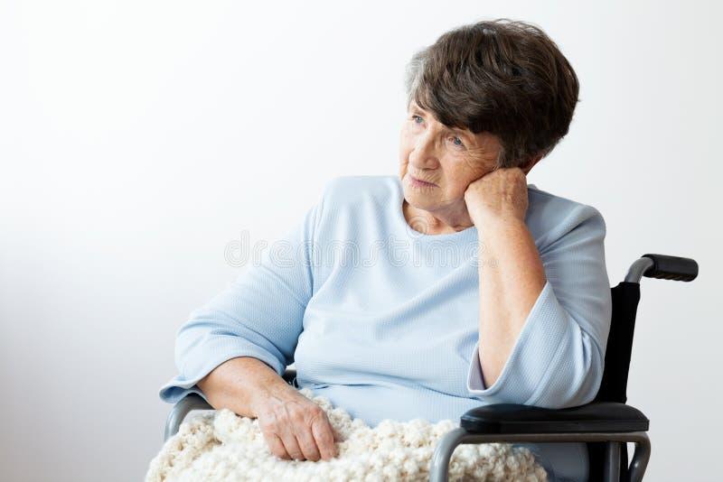 Femme supérieure handicapée triste dans un fauteuil roulant contre le backgrou blanc images stock
