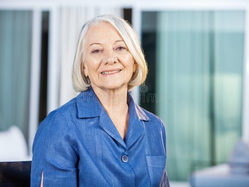 Femme supérieure heureuse à la cour de maison de repos images stock