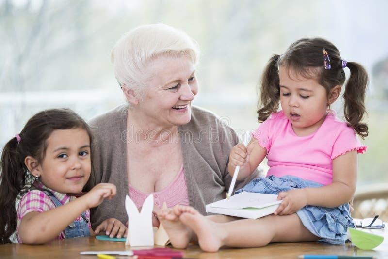 Femme supérieure heureuse avec des petite-filles faisant le travail manuel à la maison images stock