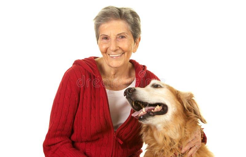 Femme supérieure heureuse avec son golden retriever photos stock