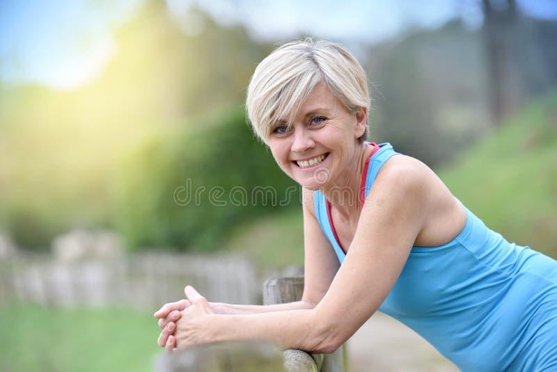 Femme supérieure heureuse détendant après avoir pulsé photographie stock