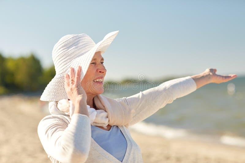 Femme supérieure heureuse dans le chapeau du soleil sur la plage d'été images stock