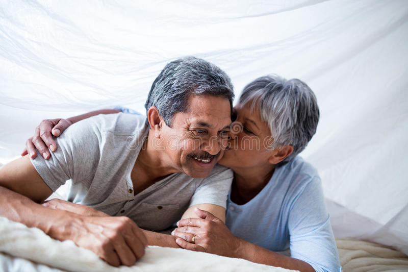 Femme supérieure heureuse donnant un baiser sur des joues de l'homme image libre de droits