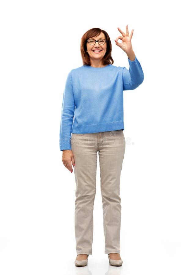 Femme supérieure heureuse en verres montrant le signe correct de main photos stock