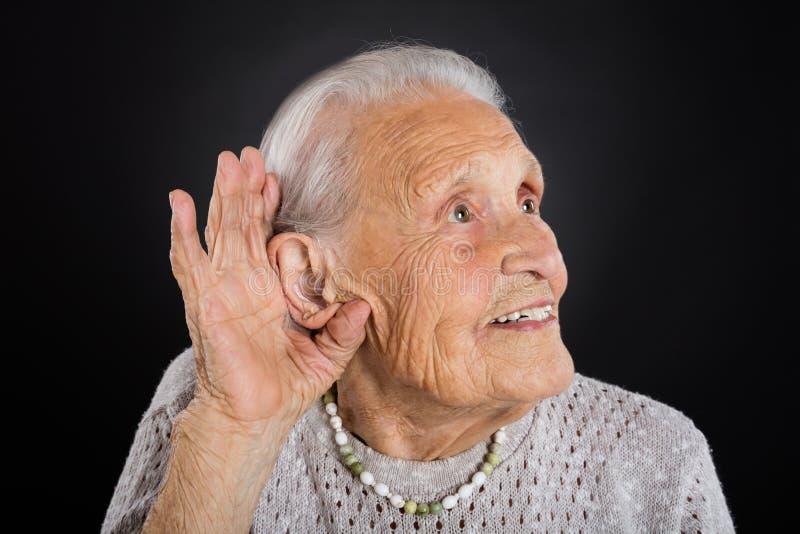 Femme supérieure heureuse essayant d'entendre photos stock