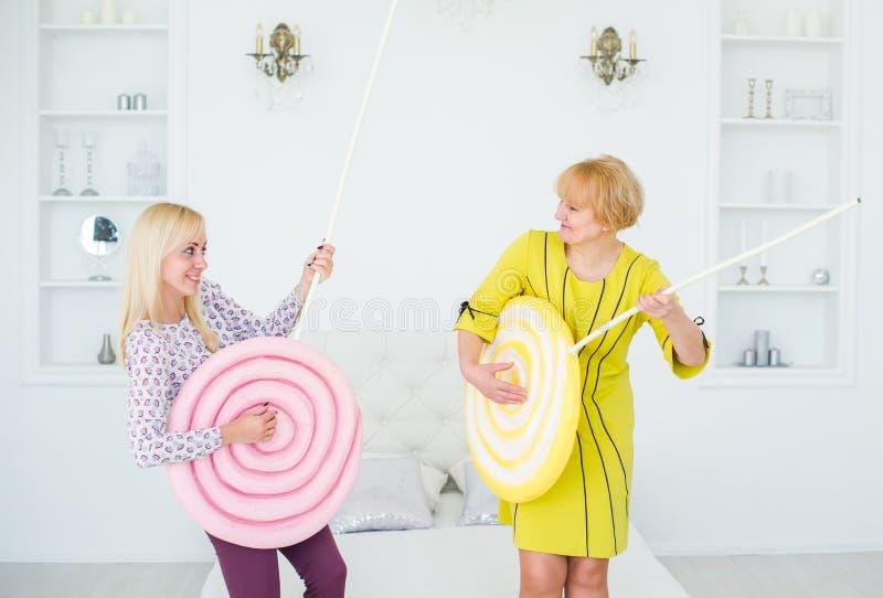 Femme supérieure heureuse et fille blonde jouant la guitare douce photos stock